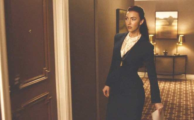 Chrysta Bell as Tammy walking up to a hotel room door with some documents