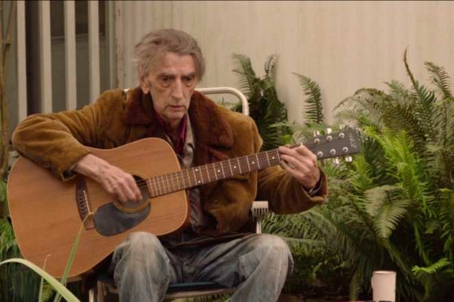 Harry Dean Stanton as Carl Rodd playing his guitar