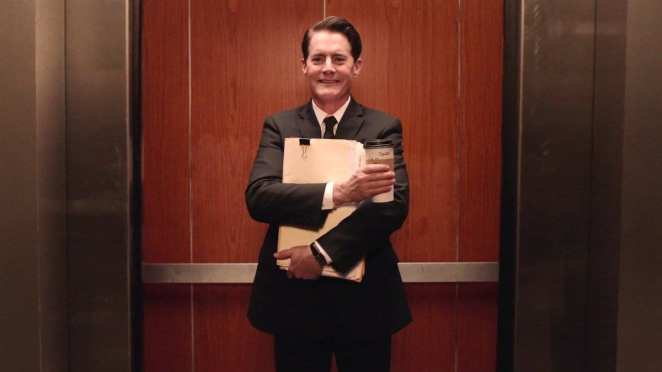 dougie cooper smiles with his coffee in his office elevator