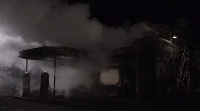 Smokes pours from the roof and windows of the convenience store