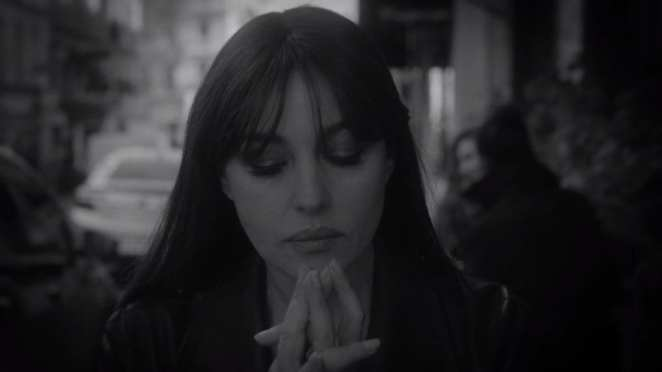 Monica Belluci sits at a table outside a cafe, looking down, her hands clasped together
