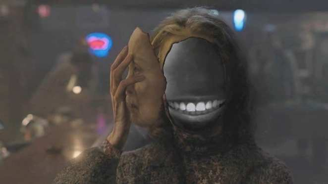 Sarah Palmer removes her face to reveal a black space with a grin