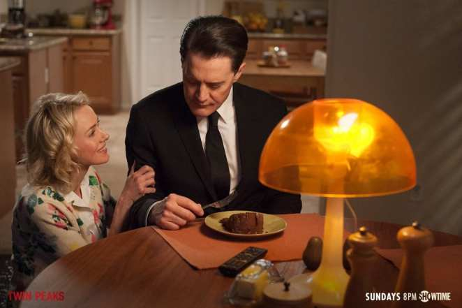 janey-e smiles and grasps the arm of dale cooper affectionately as he eats chocolate cake in their home