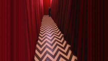 a chevron floored corridor with red curtains