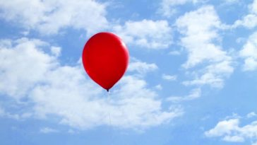 a red balloon floating in the sky