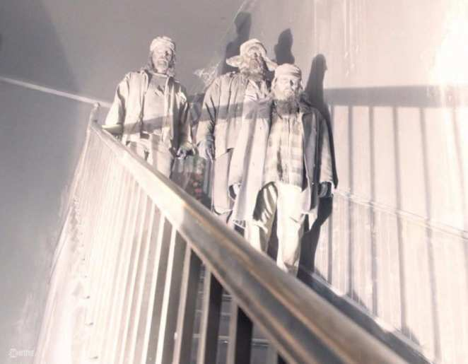 Woodsmen stand on a staircase in Twin Peaks