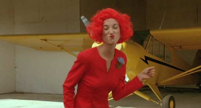 lil with a sour face and red-orange dress and hair in front of a yellow plane and wearing a blue rose