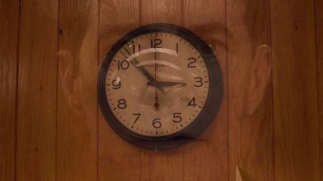 A clock shows the time hovering between 2.53 and dale coopers face superimposed over the clock