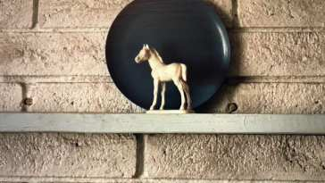 white horse figurine in front of a blue plate