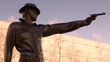 a statue of a cowboy raising his gun