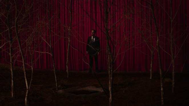 Cooper leaves the black lodge and arrives at glastonbury grove circle of sycamores. red drapes hang behind him