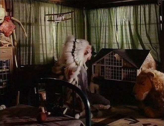 Johnny Horne wearing a Native American headdress in a play room of toys