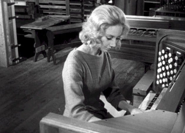 a blonde woman plays an organ in carnival of souls