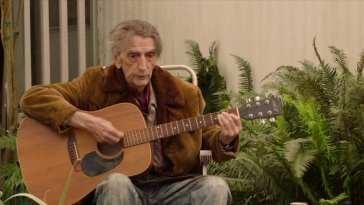 Carl Rodd plays acoustic guitar