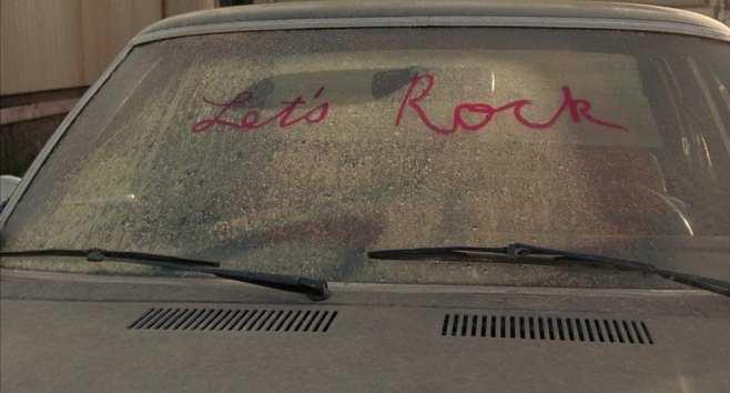 Lets Rock written on a dirty windscreen in pink lipstick