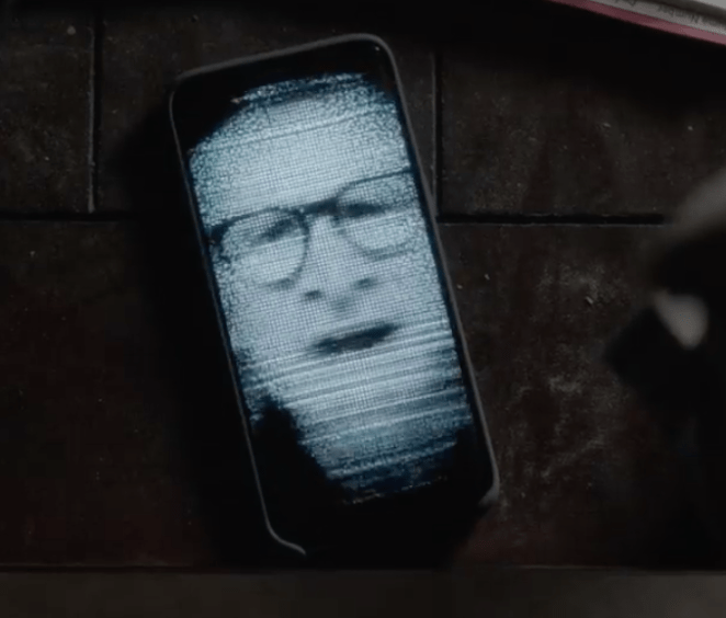 An image of a mans distorted face on a cell phone