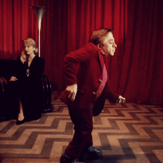 The little man from another place dances in the red room with Laura seated in the background