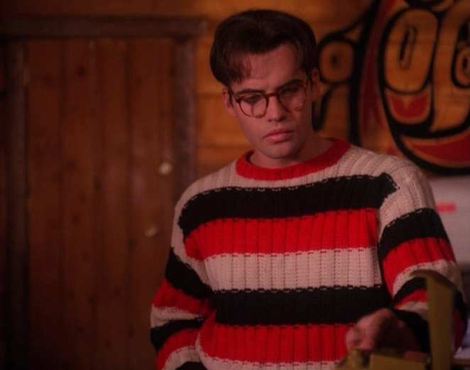 John Justice Wheeler wears glasses and a striped sweater