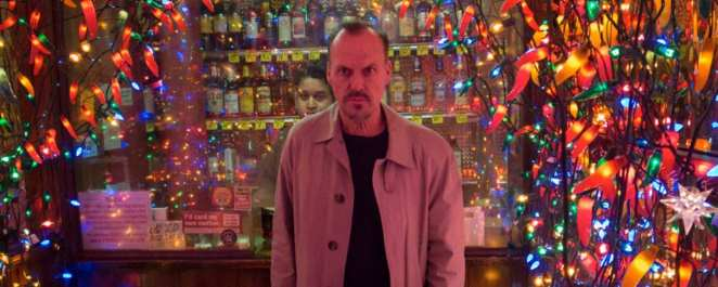 Michael Keaton stands in front of bright lights at a liquor store in Birdman
