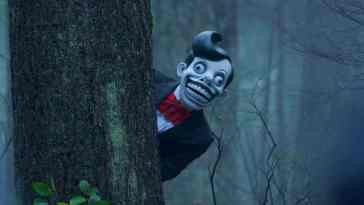 a ventriloquist dummy pops out from behind a tree