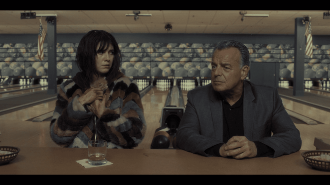 Ray Wise sitting at a bowling alley bar next to a woman holding a kitten