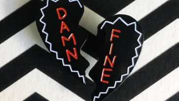 A broken heart which reads Damn Fine on a chevron background