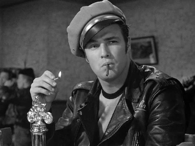 Marolon Brando wears a leather jacket with a brown hat, cigarette in his mouth and lit match in his hand.
