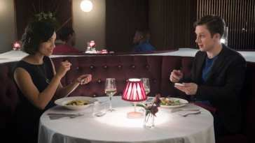 Frank and Amy prepare to look at the expiry dates on their phones as they prepare to eat at a restaurant on their first date