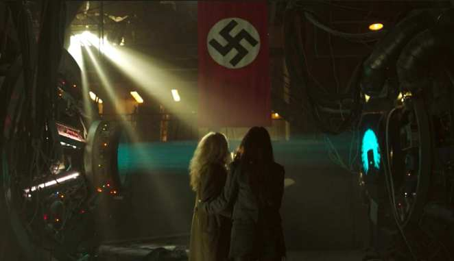 2 women hug in fear in front of a Nazi flag