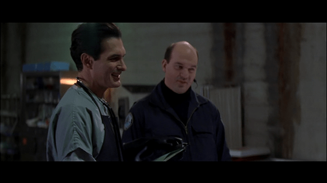 Joe Bob Briggs in the film Face-Off, playing a coroner standing next to cop.