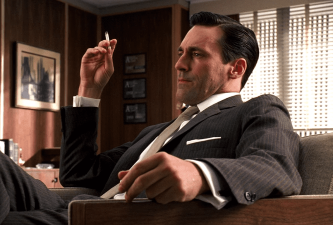 Don Draper sits in a chair smoking a cigarette