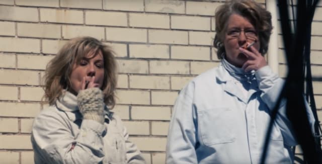 Members of the Guilty Remnant smoke in front of a brick wall