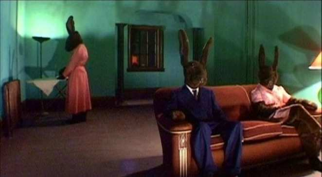 Two humanoid rabbits sit on a couch while a third irons in the background