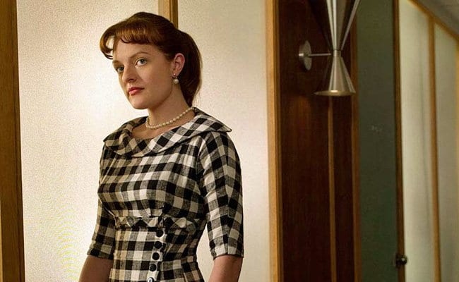 Peggy Olson standing in a door way wearing checkered print dress