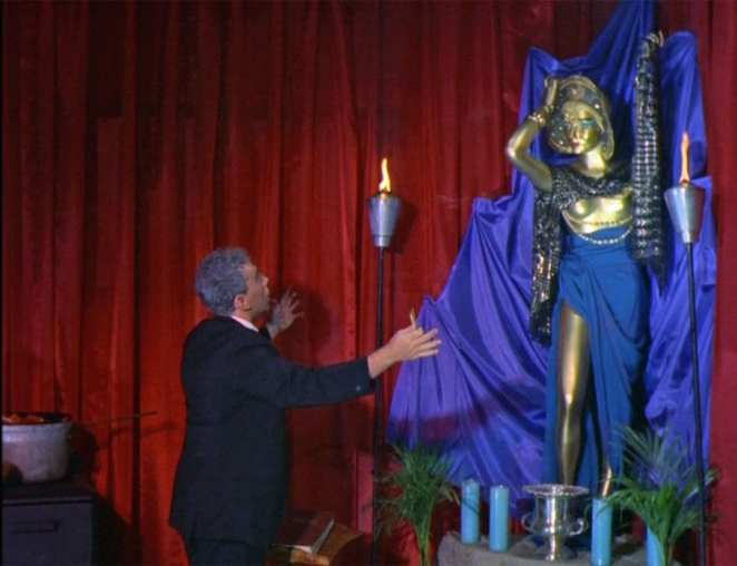 Gordon Hershell Lewis arms open worshipping a gold statue of a woman draped in blue silk