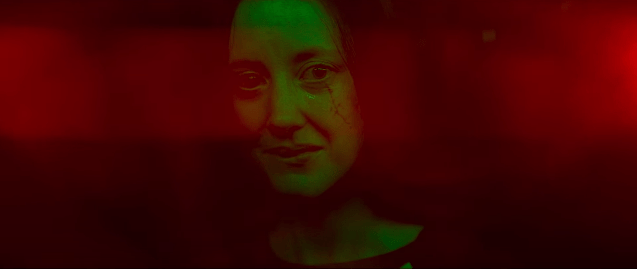 mandy's face lit green with red background