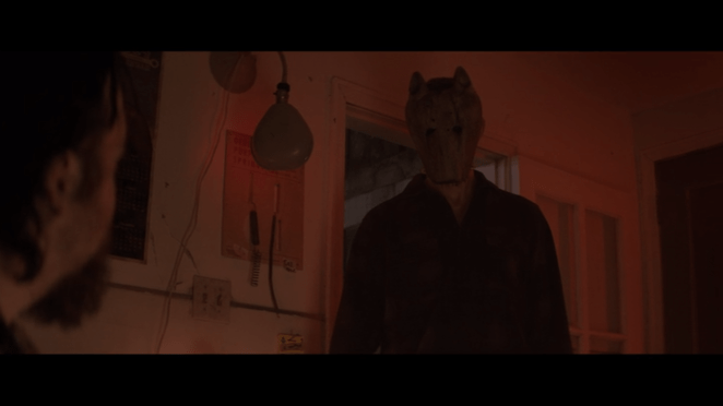 a man wears a wooden wolf mask in hold the dark
