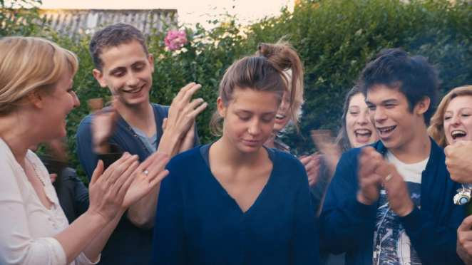 Adèle Exarchopoulos asAdèle being clapped by a crowd of people laughing in Blue Is the Warmest Colour