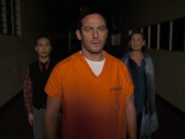 Michael is wearing an orange jumpsuit with the therapists from both of his realities behind him