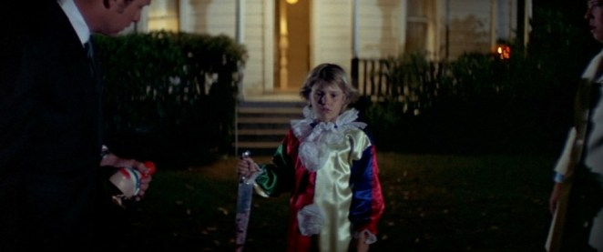 A young Michael Myers in a clown suit holding a knife after murdering his sister