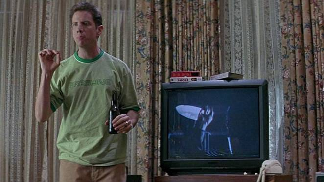 a teen with a bottle of beer stands next to a TV with the image of a man with a knife on the screen