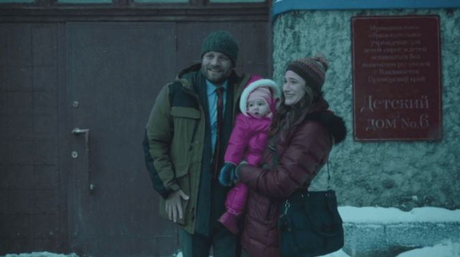 a man and a woman pose for a photo with their adopted baby in the cold outside a Russian orphanage joe anka kathryn hahn jay r. ferguson The Romanoffs