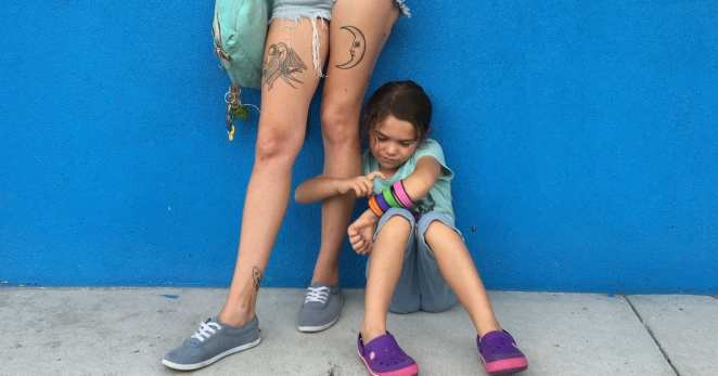 Brooklynn Prince as stars Moonee who holds her mothers leg in The Florida Project