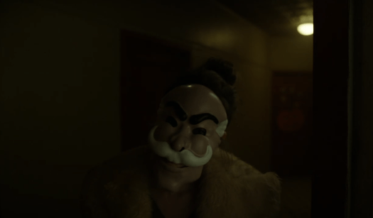 """Darlene (Carly Chaikin) wears the mask from """"The Careful Massacre of the Bourgeoisie"""" as she greets Elliot (Rami Malek) in USA's Mr. Robot"""