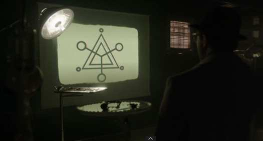 Hynek looks at suspicious triangular imagery with three circle points at the tips projected on a screen.