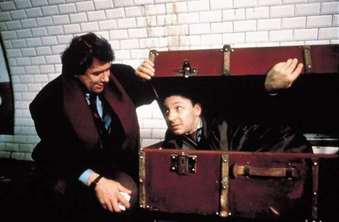 Zbigniew Zamachowski as Karol Karol with a man inside a suitcase