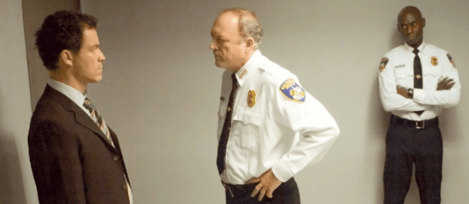 Bill Rawls stares at Jimmy McNulty, with Cedric Daniels looking on with his arms crossed