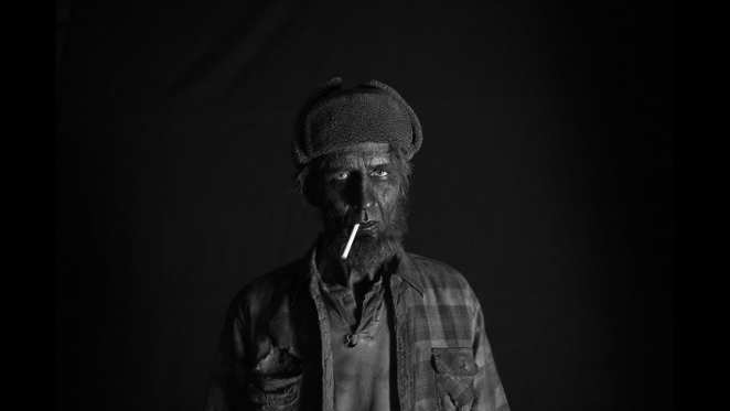 the woodsman, black from head to toe and with a cigarette in his mouth