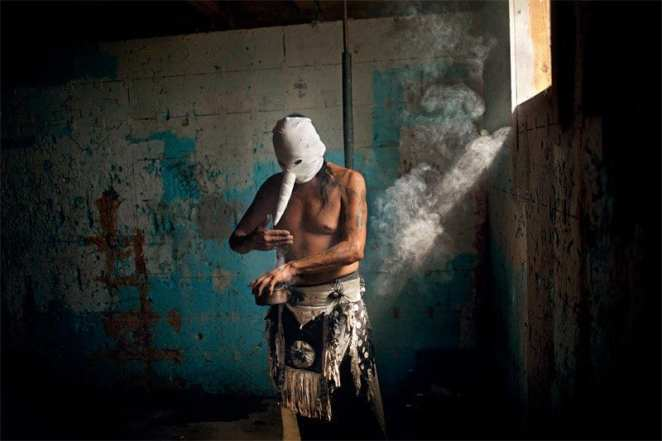 A Heyokah wears a white mask with protruding nose while making a potion
