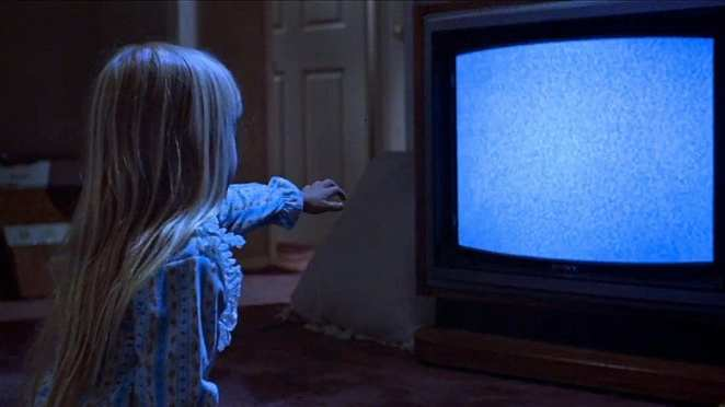 Carol Anne reaching out to a TV set in Poltergeist